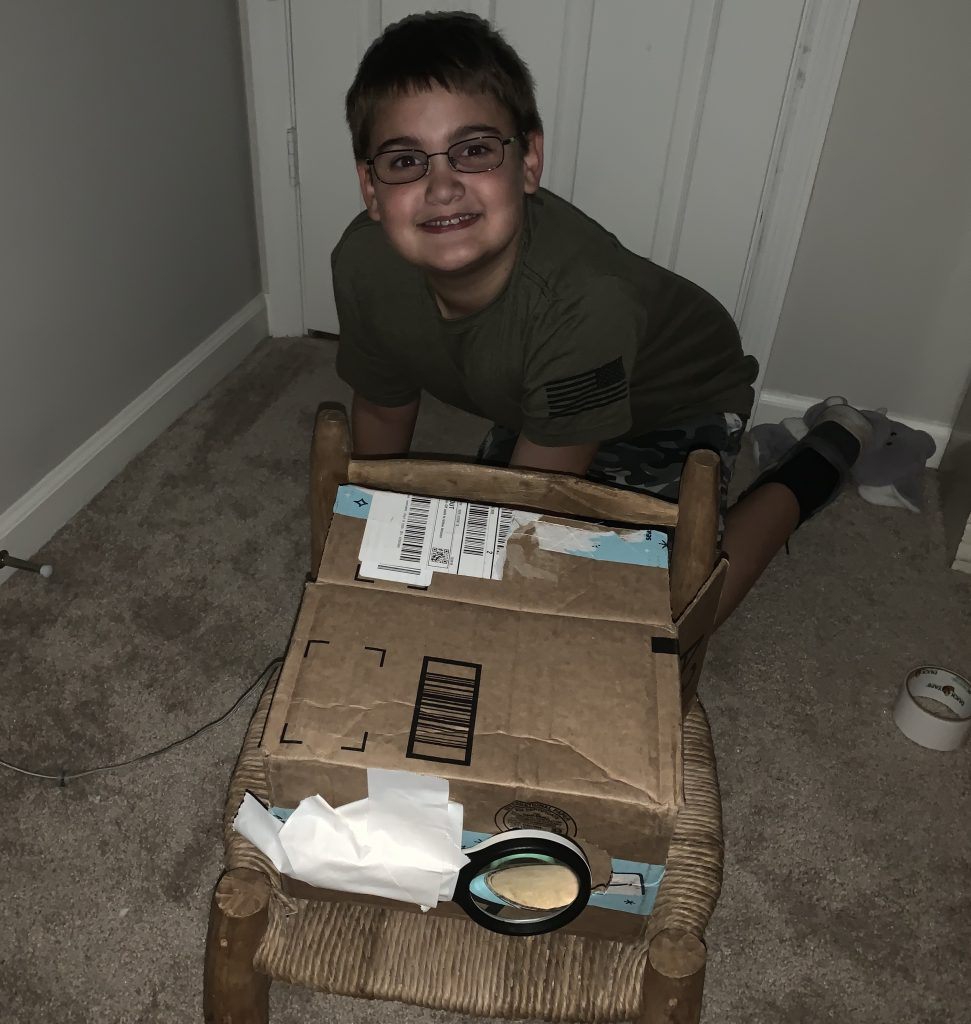Young boy smiling while showing off homemade projector