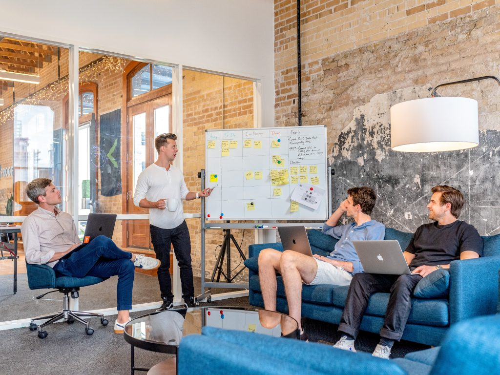 Four men in a meeting, brainstorming on a white board with sticky notes.