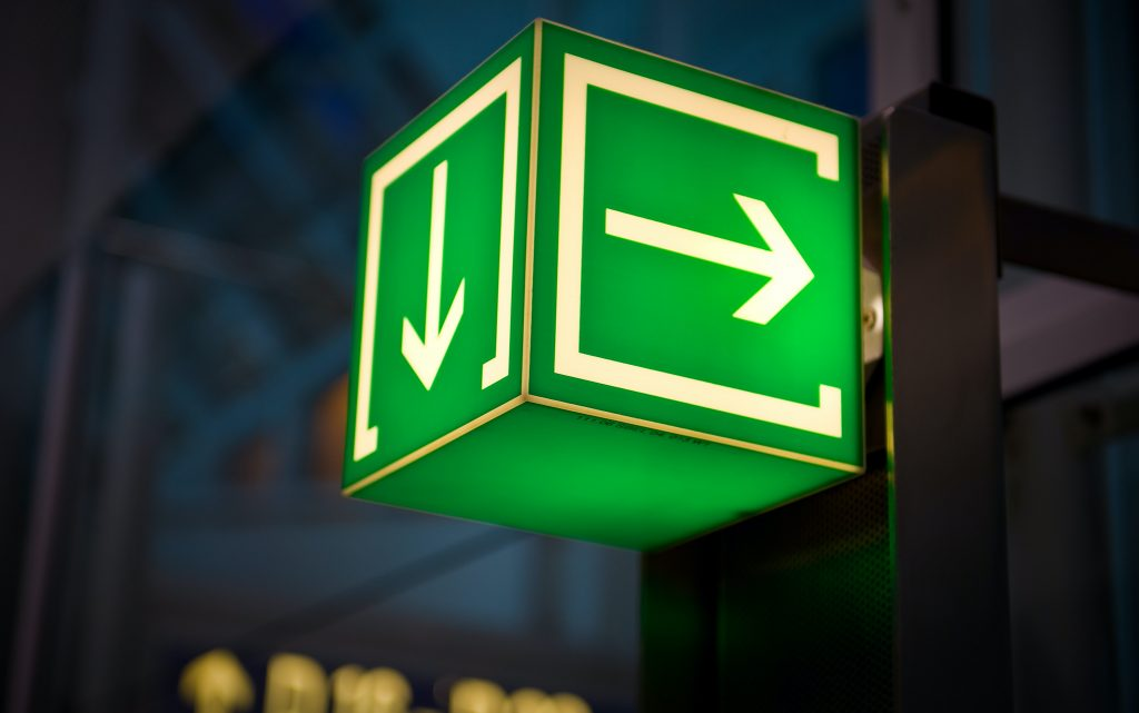 A green sign in the shape of a box with arrows on each side lighting up