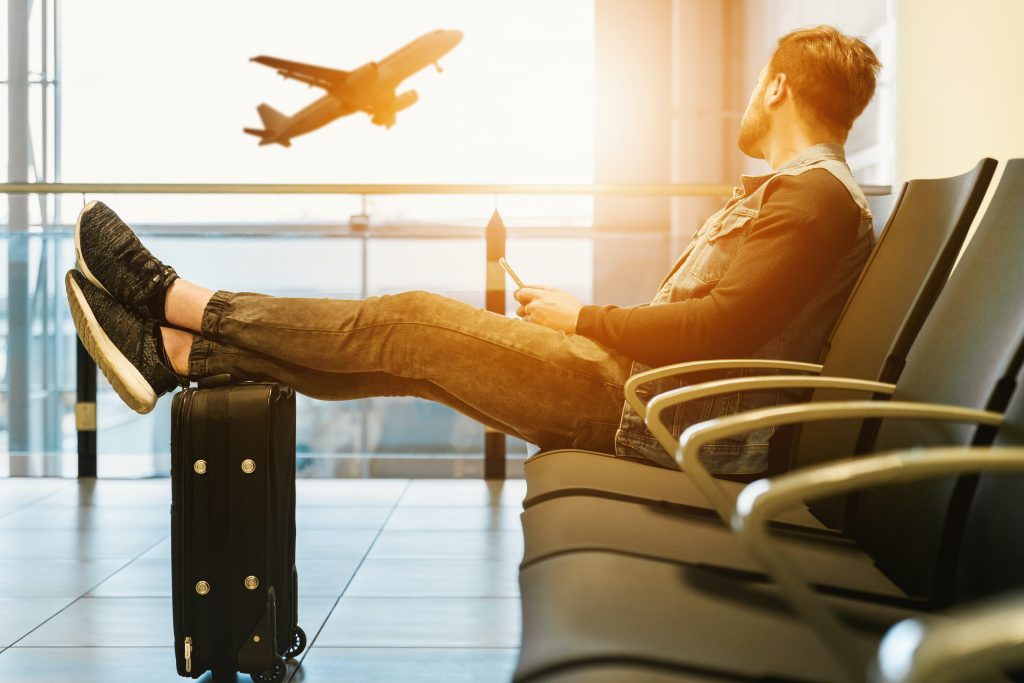 Man sitting in airport terminal with feet up on suitcase looking out the window as a plane takes off.