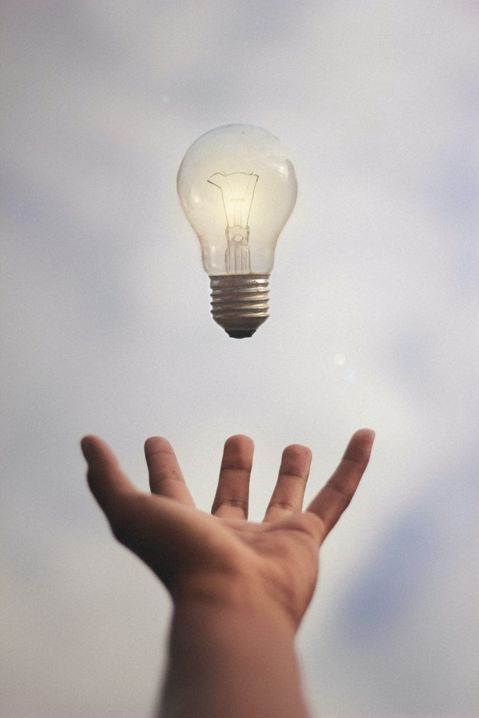 A lit lightbulb hovers above an outstretched hand.