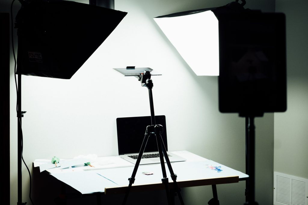 Laptop on a table surrounded by two studio lights. There is a white backdrop behind the table.