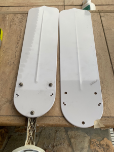 Two white fan blades lying side by side with 3 holes drilled into each one.