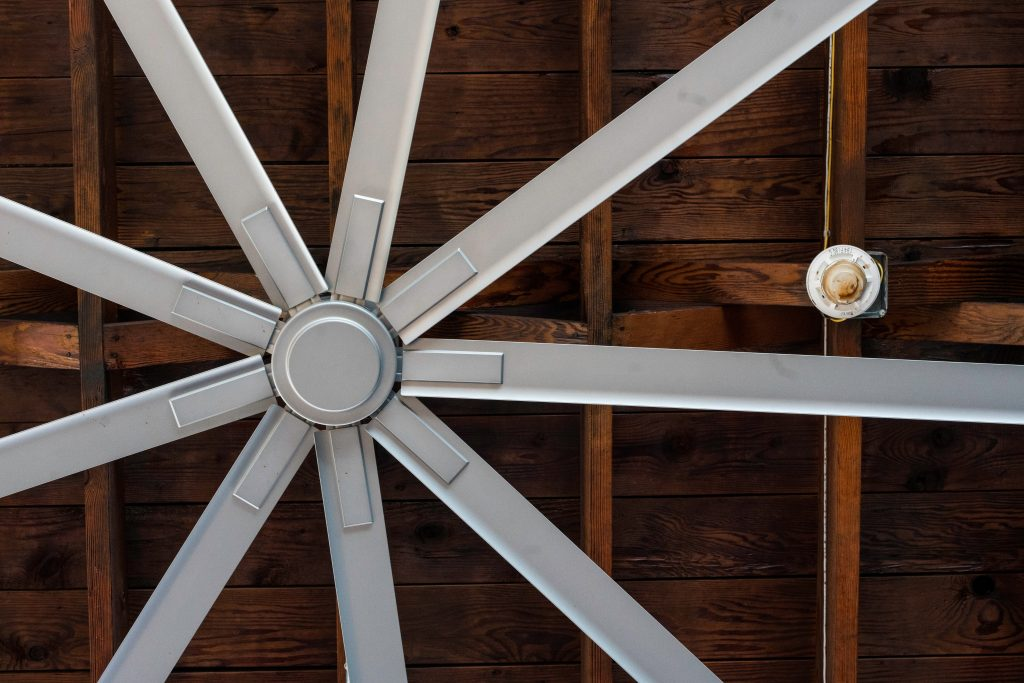 Nine bladed silver industrial fan against a wood ceiling.
